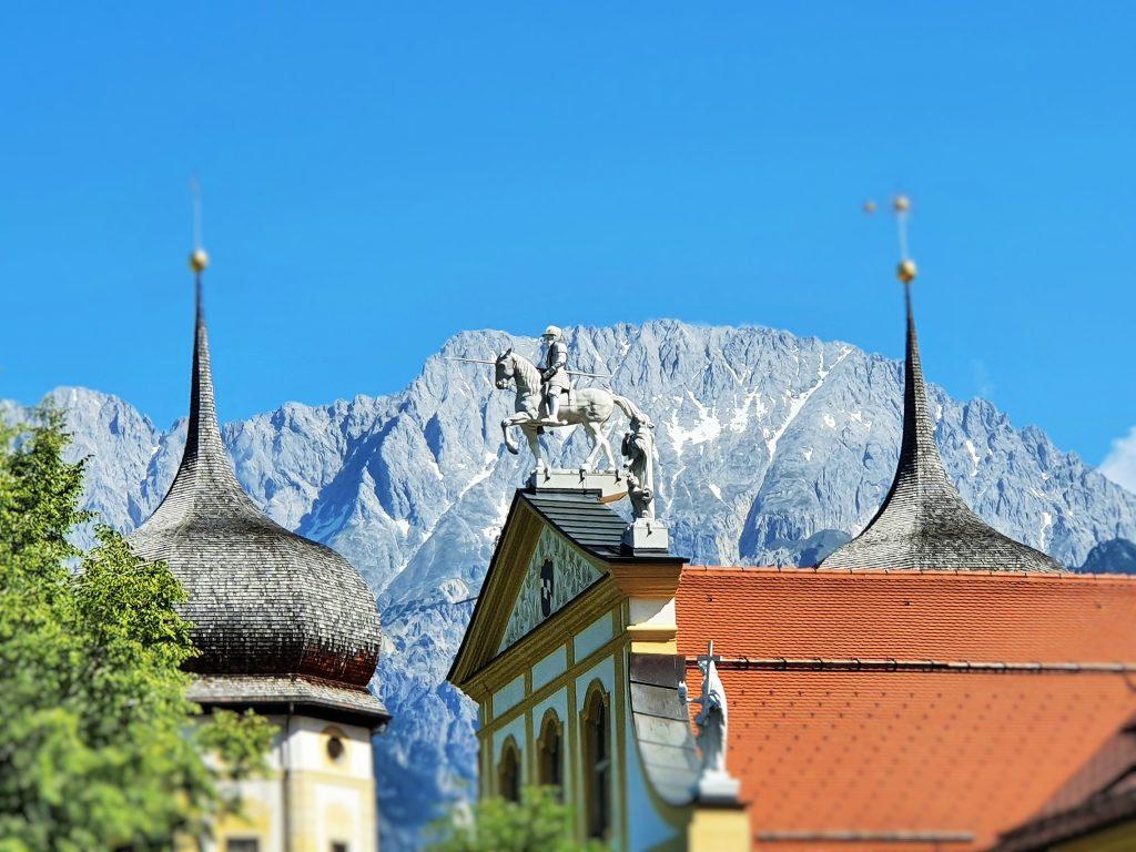 Giebel mit einem Reiterstandbild, im Hintergrund Tiroler Berge