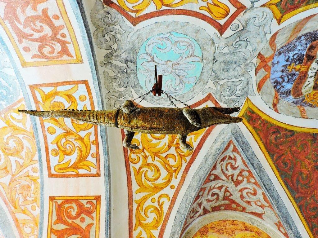 hängender Drache unter dem Eingang einer Burg