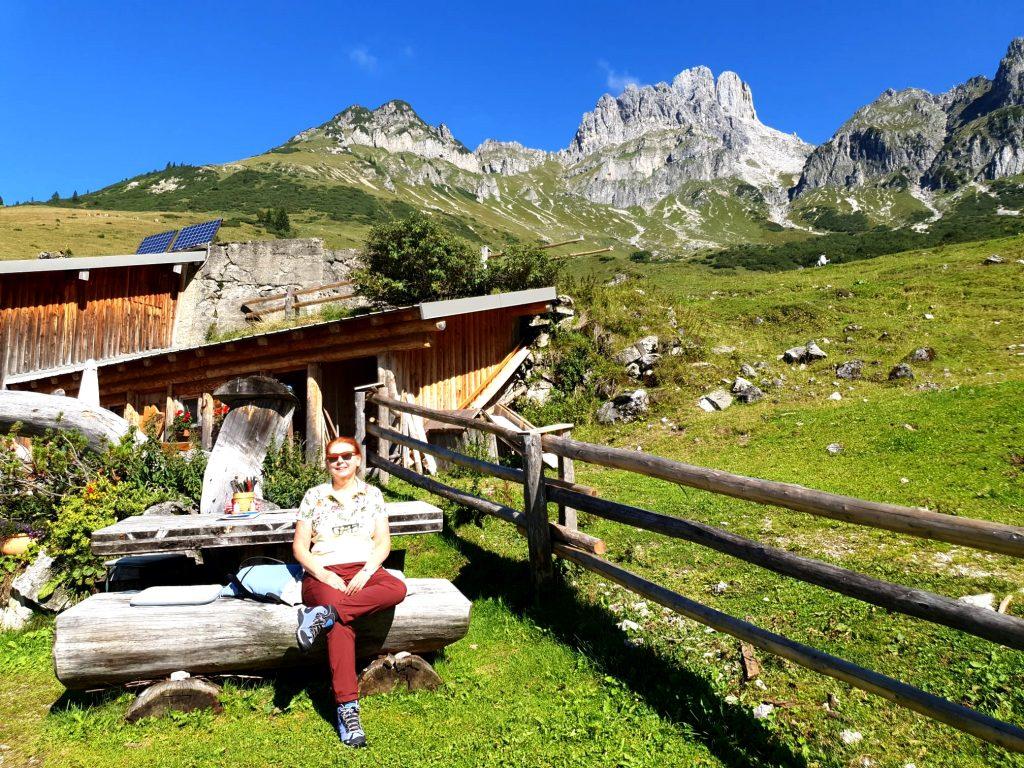 Wanderin sitzt vor einer Almhütte, dahinter Berge